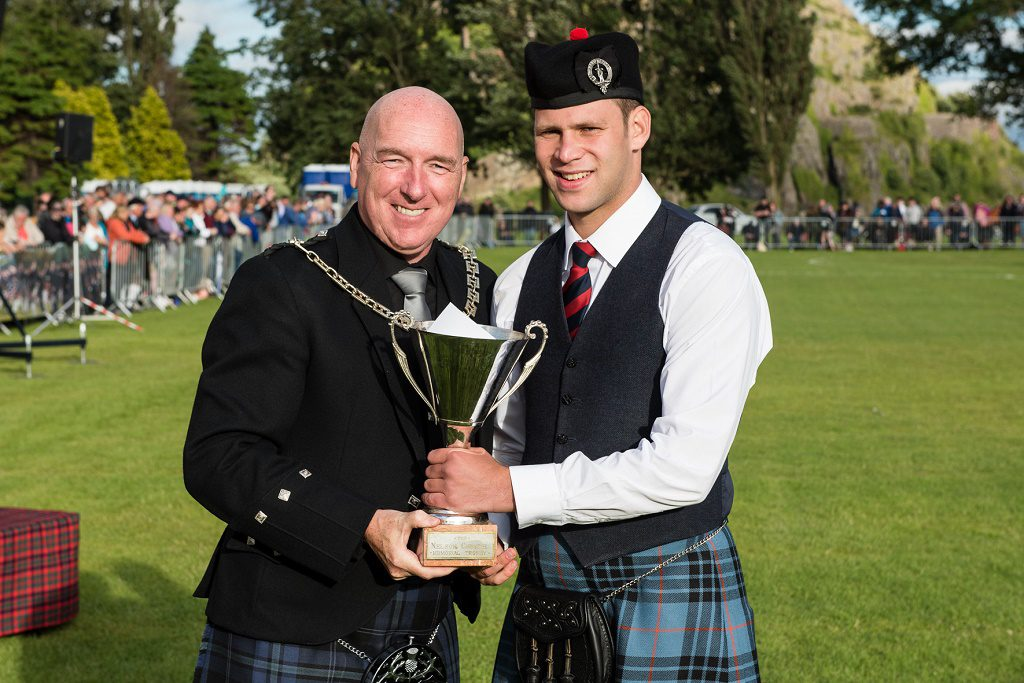 Shows Pipe Major Keith Bowes Jr picking up the Grade 2 third place trophy.