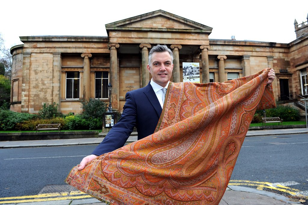 Cllr Mark Macmillan at Paisley Museum with a Paisley shawl