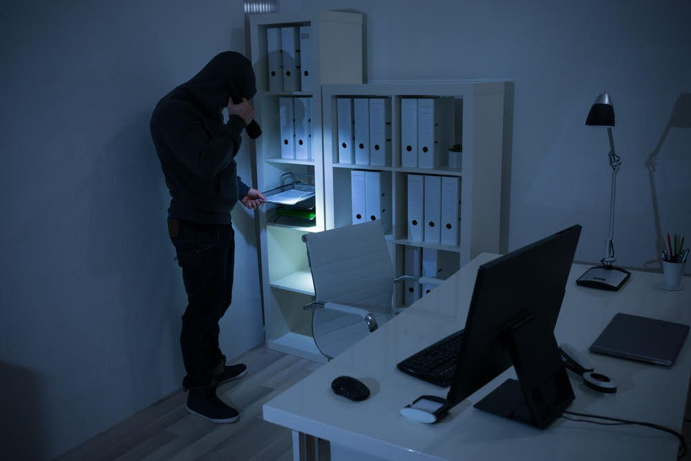 Robber with flashlight searching for documents in office at night