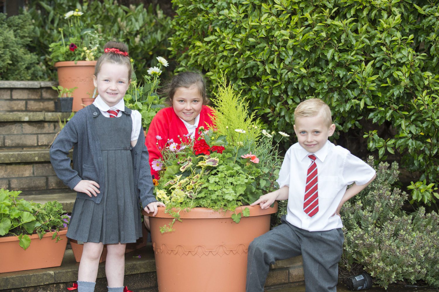 Captions Garden 1 pic: General manager at intu Braehead, Gary Turnbull with Caragh Moohan, aged five and six-year-old Kodey McDonald. Garden 2 pic: Pupils Caragh Moohan, aged five; Lucy McLay, aged nine and six-year-old Kodey McDonald enjoy their refurbished garden after it was vandalised. Thanks pic: Pupils at St Paul's Primary made 'thank you' cards for intu Braehead general manager, Gary Turnbull, second from left in back row and Drew Gallagher, a director with Cardwell Nurseries, left.