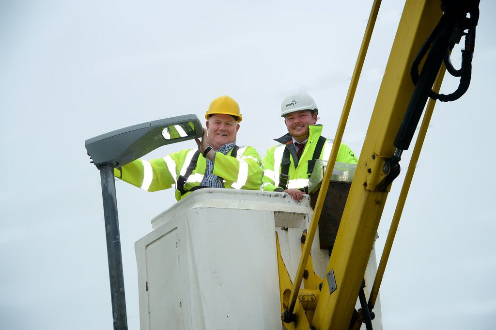 Councillor Eddie Devine (left) fitting one of the new LED lamps
