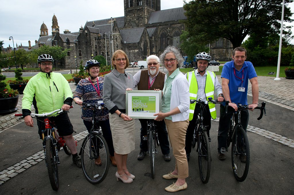 orothy Hawthorn (L) receives the Cycle Friendly Employer award from Laura Carswell (R) outside Renfrewshire House in Paisley. The photo also shows members of Renfrewshire Council staff