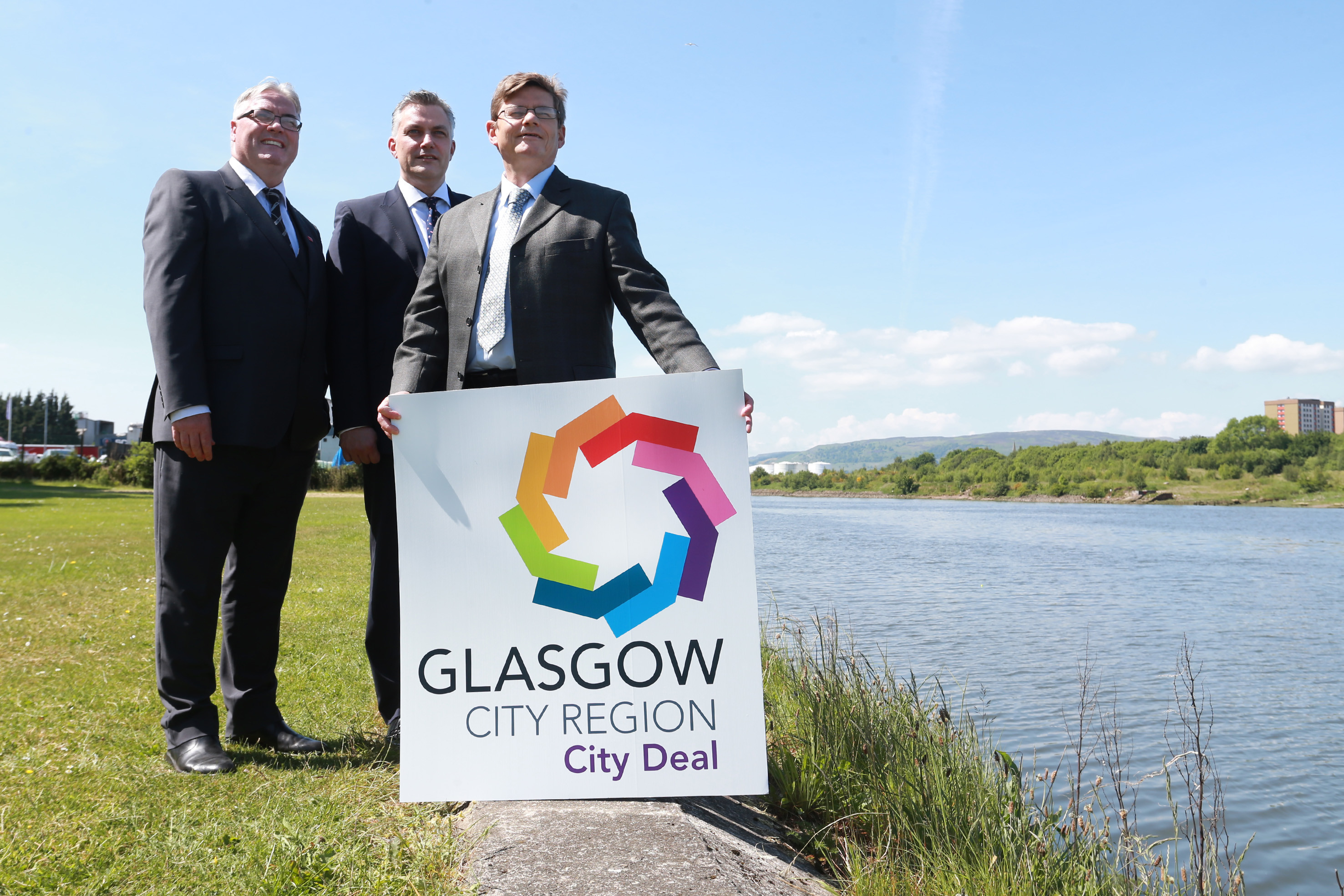 """New City Deal Clyde Bridge-SA001.JPG  FREE FIRST USE Councillor Frank McAveety, Leader of Glasgow City Council , Councillor Martin Rooney, Leader of Dunbartonshire Council and Councillor Mark Macmillan, Leader of Renfrewshire Council  at the banks of the clyde near where the New City Deal Clyde Bridge is to nee located. Council Leaders Back New City Deal Clyde Bridge Three council Leaders have teamed up to look at possible locations for a new bridge across the Clyde.The new bridge will be part of the £78 million Clyde Waterfront and Renfrew Riverside Project and funded by Glasgow City Region City Deal.  The Leaders of West Dunbartonshire, Glasgow City and Renfrewshire Councils believe that it will bring 'significant investment, jobs and transport benefits to communities on both sides of the river and throughout the City Region.'This will be an exciting addition to the Clyde and its only opening road bridge. It will also be the only road crossing between the Clyde Tunnel and the Erskine Bridge. Councillor Martin Rooney, Leader of Dunbartonshire Council said, """"This landmark bridge will put our communities right at the heart of the regional economy.  It will have a positive impact on local life and help to create a thriving future where businesses can grow and residents can take advantage of new connections to employment, leisure and educational opportunities.""""The project will increase the potential for business growth by improving their connections with customers and suppliers.  It will also enhance access to land which is currently underused or derelict; unlocking the potential for regeneration and new developments in the Yoker, Clydebank and Renfrew areas.The Glasgow City Region City Deal is investing £1.1 billion on infrastructure. £300 million of this will be spent on projects in Dunbartonshire and Renfrewshire: the £28m Exxon site development at Bowling, the Glasgow Airport Investment Area, and the new rail connection between Glasgow Central, Paisl"""
