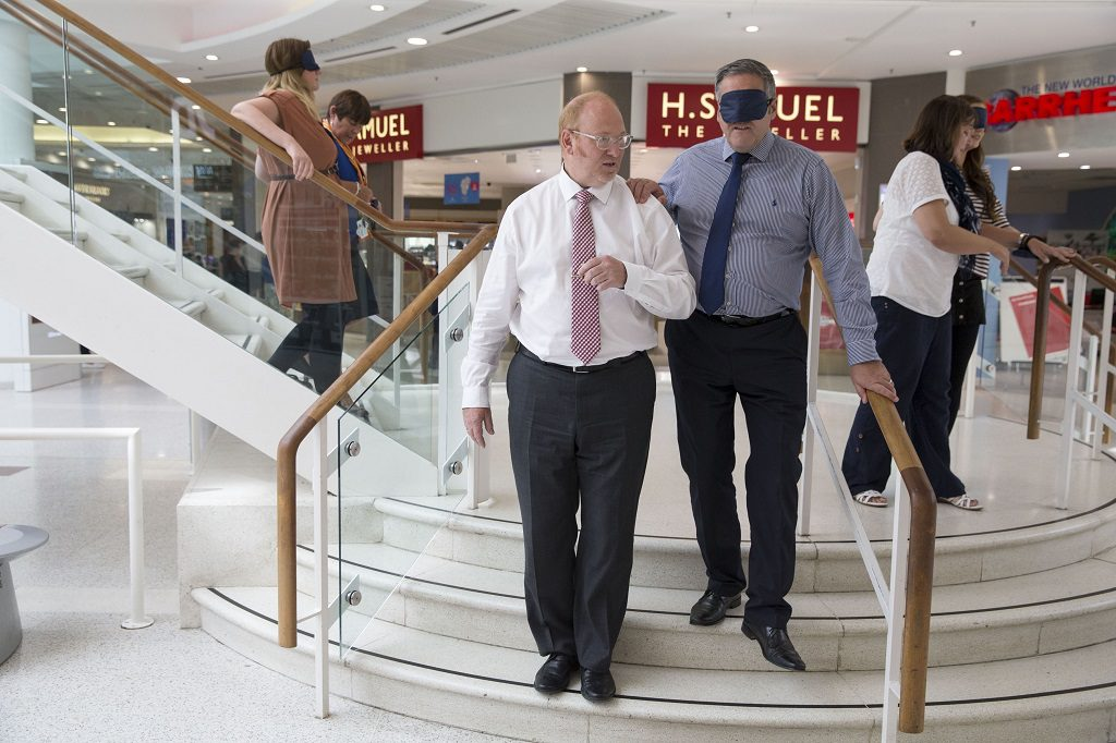 Blindfold intu Braehead boss, Peter Beagley is led through the mall by guest services manager, Bruce Harley during the Visibility training session.